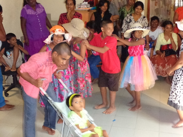 The children performing at a party at E.A.S.E. They are enacting a children's song about a doll. Little Dulhara who has severe Cereral Palsy and is unable to walk though she can talk is playing t